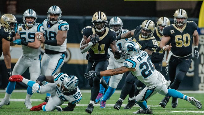 New Orleans Saints running back Alvin Kamara (41) runs past Carolina Panthers free safety Kurt Coleman (20) during the second half at the Mercedes-Benz Superdome.