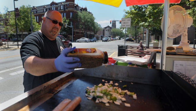 Greg Fahnestock, owner, adds spices to hotdog toppings on the grill Tuesday on The Haute Doggerie food cart in downtown Chillicothe.
