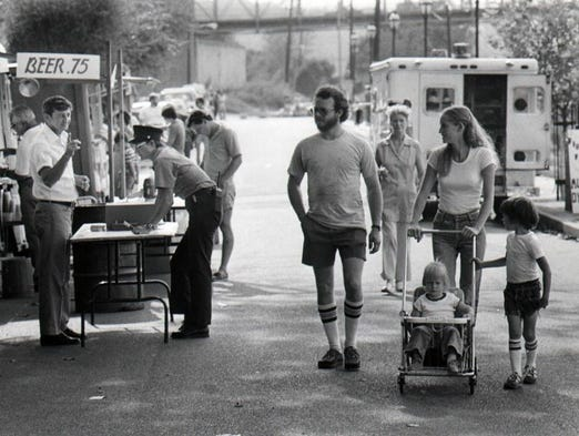 Man at a booth tries to interest Fred and Debarah Murphy and children Sean, 5, and Angela, 2, of Covington. Grandmother June Dameron of Covington is pictured in background between Fred and Debarah, August 31, 1980.