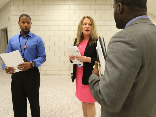 Edison Tech principal Walter Larkin Jr., far left, and Assistant Principal Jacob Scott give Barbara Deane-Williams a tour of the school that includes some of the programs offer to students.
