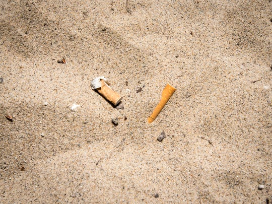 Cigarette butts in the sand Monday, June 11, 2018, on the beach at Fort Gratiot County Park. The county is working to ban smoking from its parks.