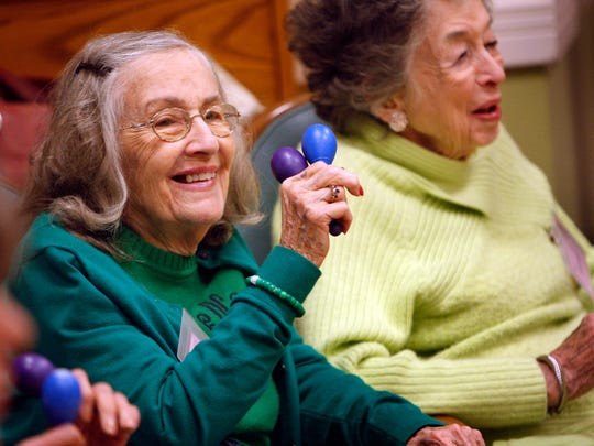 Eva, a client at the  Page Robbins Adult Day Center, participates in a sing-a-long at the center on Wednesday.