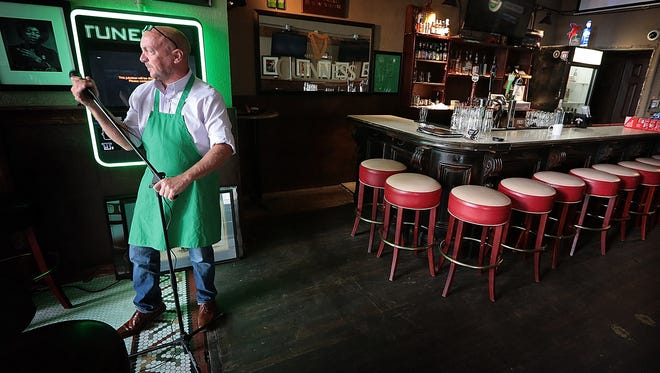 Seamus Loftus, owner and operator of The Brass Door restaurant on Madison Avenue, straightens up the Irish pub after a musical gathering Tuesday night. Loftus finished an expansion of the pub over the summer, mirroring the fast expansion of businesses in the downtown Memphis area.
