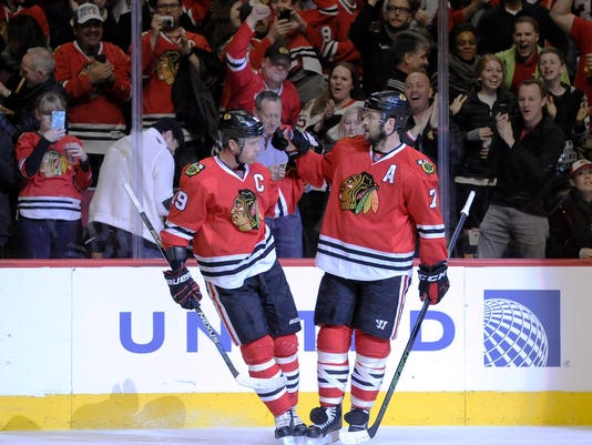 Chicago Blackhawks center Jonathan Toews (19) celebrates his goal against the Arizona Coyotes with Chicago Blackhawks defenseman Brent Seabrook (7) in the first period of an NHL hockey game Tuesday, April 5, 2016, in Chicago. (AP Photo/David Banks)