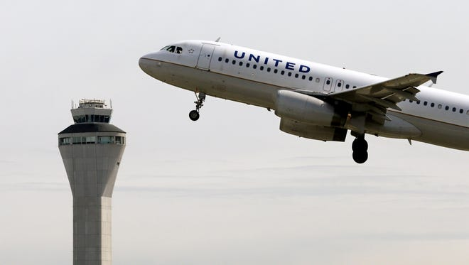 A United Airlines jet departs in view of the air traffic control tower at Seattle-Tacoma International Airport in Seattle in 2013. United has canceled flights out of three major New York City area airports ahead of Winter Storm Juno