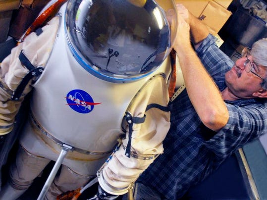 Ken Havekotte, owner of Space Coast Cover Service, shows off a spacesuit used in the 1980s for application research in