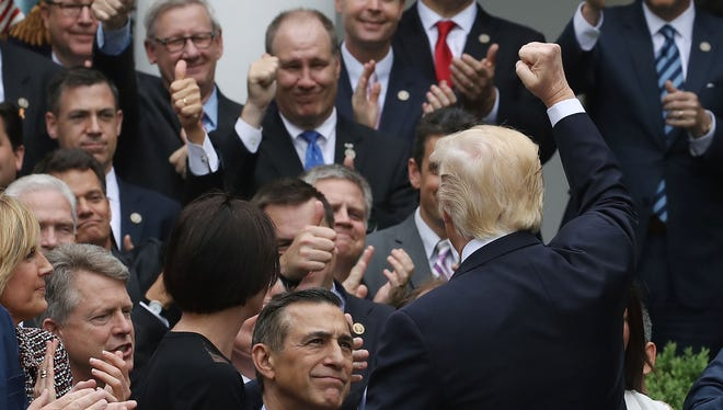 President Trump congratulates House Republicans after they passed legislation aimed at repealing and replacing Obamacare, during an event in the Rose Garden at the White House on Thursday.