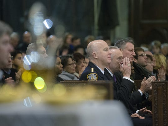NYPD Commissioner Bill Bratton, acknowledges Catholic Cardinal Timothy Dolan, not pictured, as he is requested to reaffirm the city's appreciation for the NYPD alongside NYPD's Chief of Department James O'Neill, center, and New York City Mayor Bill de Blasio, right, during mass at St. Patrick's Cathedral, Sunday, Dec. 21, 2014, in New York. The previous day an armed man walked up to two New York Police Department officers sitting inside a patrol car and opened fire Saturday afternoon, killing both before running into a nearby subway station and committing suicide, police said. (AP Photo/John Minchillo)