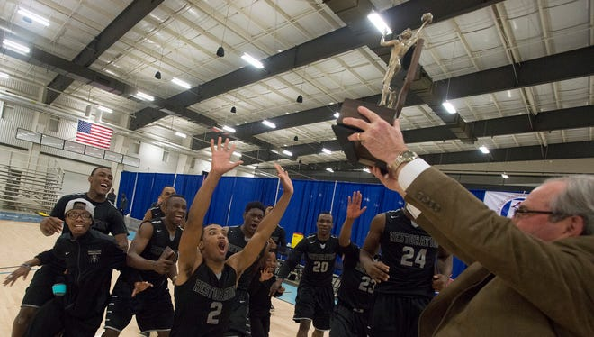 Restoration's Jeremy Pinder (2) raises his hands as the team rushes towards the AISA Class AA State Championship trophy on Thursday, Feb. 12, 2015, at the Multiplex at Cramton Bowl in Montgomery, Ala.