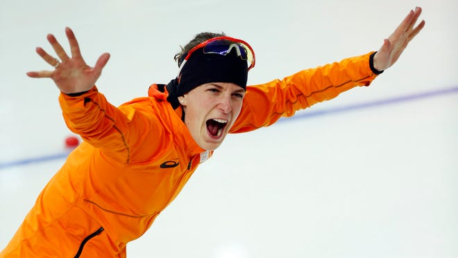 Irene Wust of Netherlands celebrates after winning speed skating's 3,000 meters gold medal.