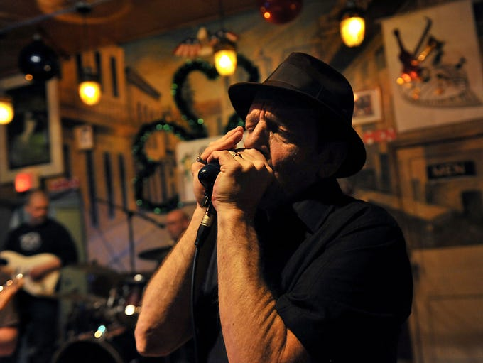Musician Pat Prentice wails on his harmonica at the