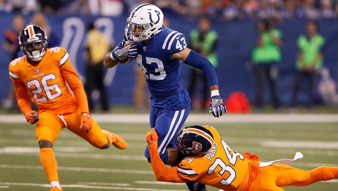 Indianapolis Colts tight end Ross Travis (43) attempts to run out of the tackle by Denver Broncos defensive back Will Parks (34) in the first half of their game against the Denver Broncos at Lucas Oil Stadium Thursday, Dec 14, 2017.