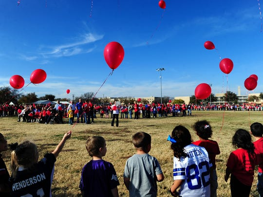 """Thomas Elementary School students release balloons to honor Rex Fleming, their 10-year-old friend who died this week after fighting brain cancer for two years. Rex's favorite song, """"LIfesong,"""" by Casting Crowns was playing while the balloons were released on Friday, November 30, 2012 at Thomas Elementary School. Thomas Elementary Principal David Adams explained to the students why they were standing in a circle formation during the tribute to Rex. """"Circles represent never ending life, friendship and love,"""" Adams said."""