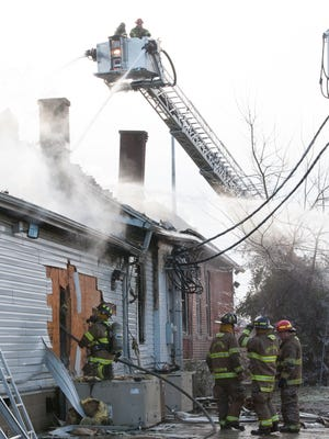 Firefighters work from the ground and sky to battle the fire at Bronze By The Bricks tanning salon Friday morning.