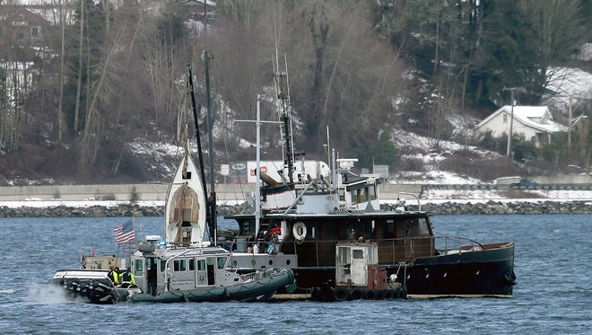 The Kitsap County Sheriff's Office boat examines a deserted boat Tuesday in Sinclair Inlet.