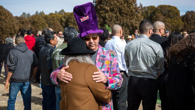 Jim Bole, who knew Miguel Silva for over 30 years, comforts a fellow mourner during Silva's funeral at Hillcrest Memorial Gardens Cemetery on Saturday.