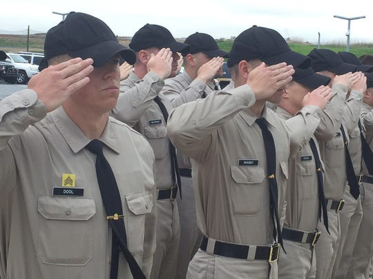 New Castle County Police Department recruits salute during a ceremony at the Paul J. Sweeney Public Safety Building in Minquadale on May 5. County Police have considered removing a college requirement for applicants who do not have four years military experience.