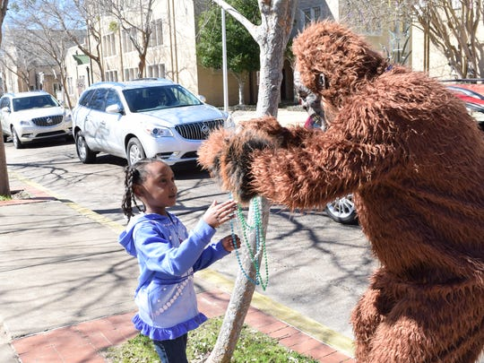 Downtown Dave, downtown Alexandria's resident sasquatch, gives Mardi Gras beads to Kenlyn Brown Tuesday while she and her mother Kiera Scott were visiting downtown Alexandria.