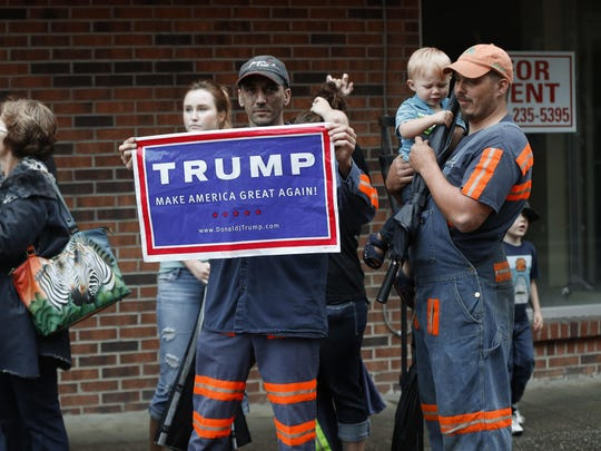 Coal miner Chris Steele holds a sign supporting Donald Trump outside a Hillary Clinton Democratic presidential candidate event in Williamson, W.V., Monday, May 2, 2016. (AP Photo/Paul Sancya)