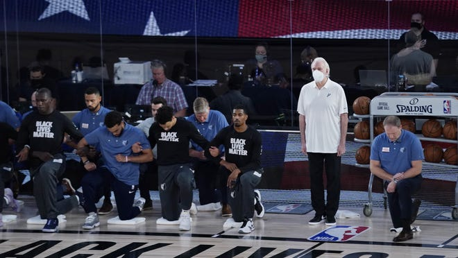 San Antonio Spurs head coach Gregg Popovich stands beside his players as they kneel before an NBA game against the Memphis Grizzlies on Sunday in Lake Buena Vista, Fla.