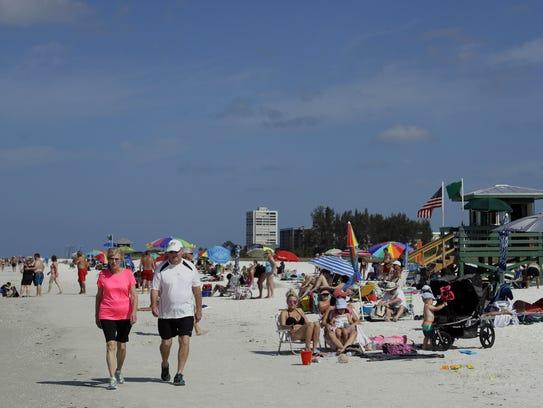 A couple strolls on Siesta Beach on Siesta Key in Sarasota,