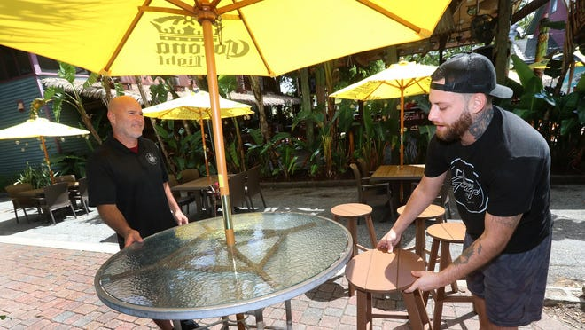 General manager Scott Smith and employee Mike Griscavage Sr., L/R, set up tables and chairs on a walkway next to the Grind Gastropub & Kona Tiki Bar, Thursday May 7, 2020. As of Friday, bars and pubs will be allowed to open at 50% capacity inside with full capacity outside, the governor said.