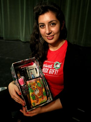 Nanor Balabanian, 25, holds the Operation Christmas Child box she received when she was young. A doll, bible and notebook were a few of the items in box.  Photo taken at Salem Academy on Friday, Oct. 9, 2015.