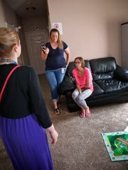 Scarlet, right, talks with Heidi Knoerzer, left, and Tasha Rihm, center, in her group home, Wednesday, June 28, 2017.  Scarlet is one of the children who has been in Indiana's foster care system the longest.  She is one who has been waiting among the longest to be adopted.