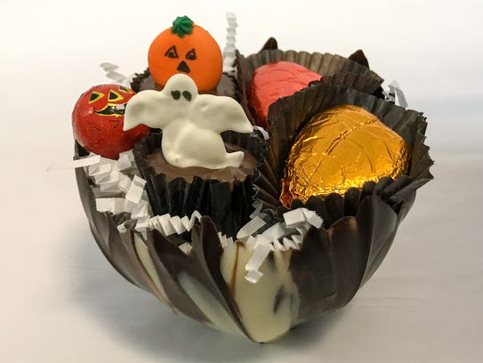 A lotus cup is filled with Halloween-themed candies at Encore chocolates.
