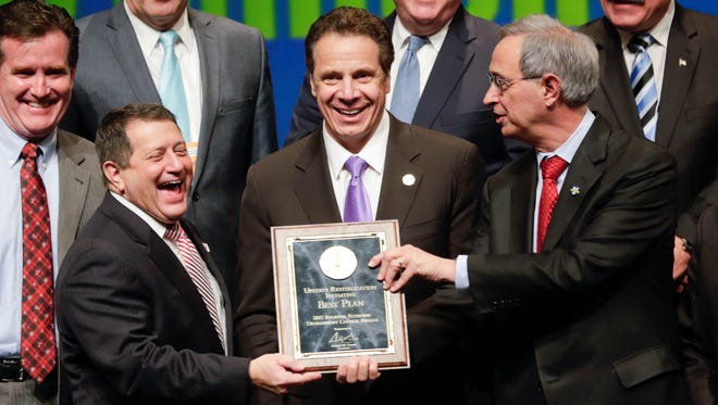 New York Gov. Andrew Cuomo, center, poses for a photo with Assembly Majority Leader Joseph Morelle, left, D-Rochester, and University of Rochester President Joel Seligman during an economic development awards ceremony on Dec. 10, 2015 in Albany.