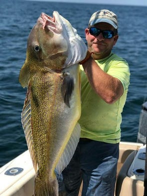 Tom Schanno holds a new state record golden tilefish.