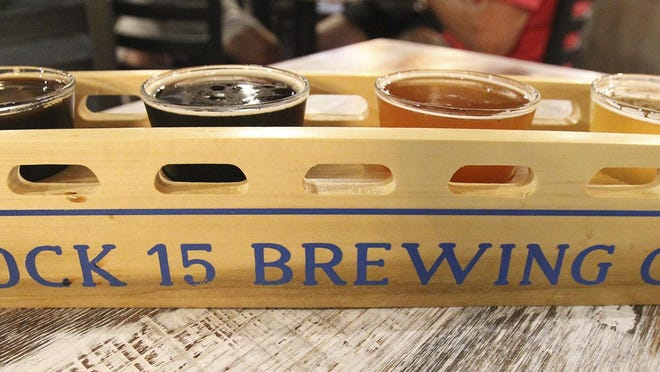 A flight of beer comes in a rack shaped like a canal boat at Lock 15 Brewing Co. in Akron.