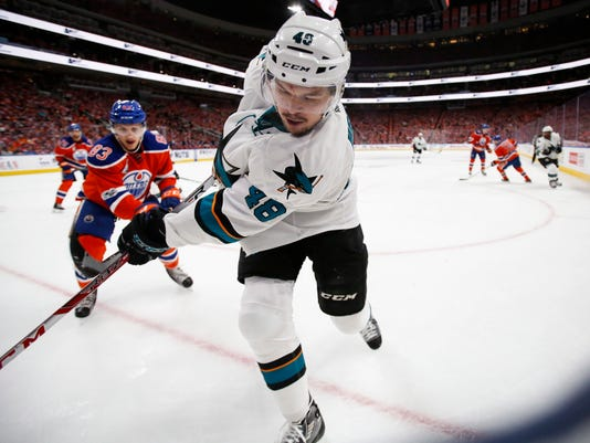 San Jose Sharks' Tomas Hertl, right, of the Czech Republic, is chased into the corner by Edmonton Oilers' Matthew Benning during the first period of Game 5 of a first-round NHL hockey Stanley Cup playoff series, Thursday, April 20, 2017, in Edmonton, Alberta. (Jeff McIntosh/The Canadian Press via AP)