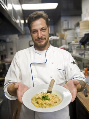 Johnny Lavoie, owner of new restaurant Nora's New York Pizzeria in Hendersonville, holds up a freshly made plate of one of his dinner specials, chicken piccata, Thursday afternoon at the restaurant.