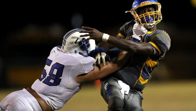 Rickards Marcus Riley is hit by Godby's Trey Laing as he throws the ball during their game at Cox Stadium on Friday night.