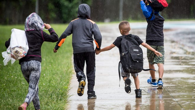 Students try to get home in the middle of the rain after dismissal at Sutton Elementary on May 24. Sutton along with three other schools won't reopen in the fall after the school board voted to close the schools and combine their students into neighboring schools.