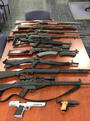 Several seized firearms sit on a table after Delaware State Police investigation into illegal gun sales on Dec. 29, 2016.
