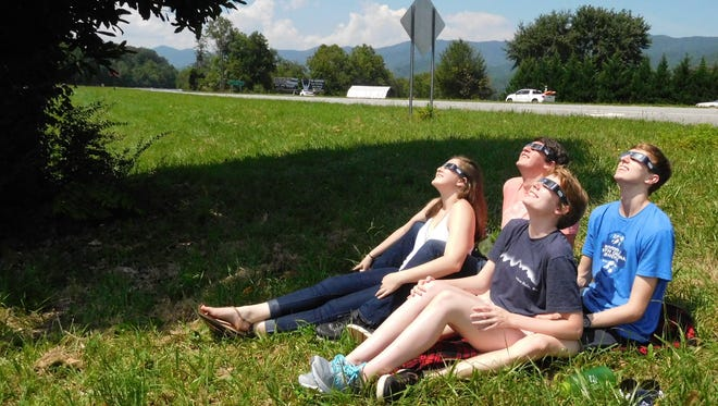 Clair Huffine, front, and three other UNC Asheville students drove out to Andrews Monday morning, found a free parking spot at a convenience store and waited in the shade of a magnolia tree beside U.S. 19-74 for the eclipse to begin.