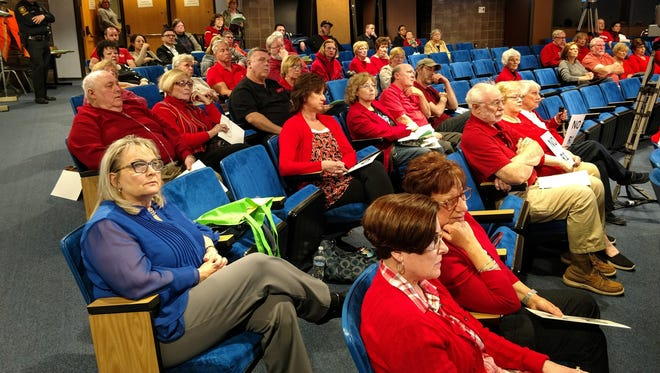 Residents who live near the former Clay Elementary School in Livonia wore red to Monday's city council meeting to protest the proposed rezoning of the school.