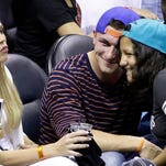NFL football player Johnny Manziel, center, poses for a photograph during the second half in Game 2 of the NBA basketball finals between the San Antonio Spurs and the Miami Heat on Sunday, June 8, 2014, in San Antonio. (AP Photo/Tony Gutierrez)  ORG XMIT: TXKJ162