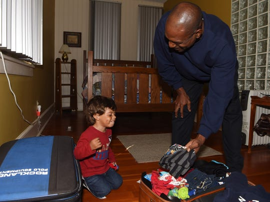 Rodrick Boney, right, shows son Kayden Boney, left, one of his favorite shirts while going through their suitcases. Those two suitcases full of belongings were all the Boney family could save from the destruction of Hurricane Harvey.