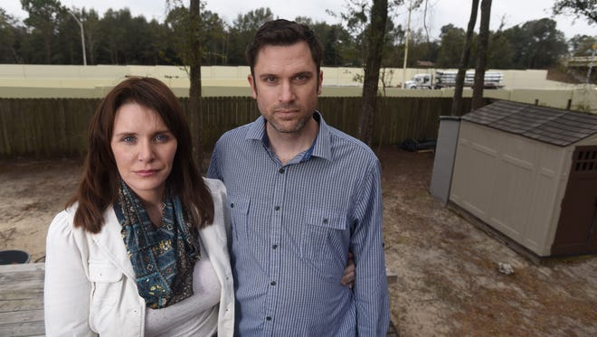 Katie and Joe Winschief stand in the backyard of their home in northern Pensacola. The couple says noise from the I-10 widening project has lowered the value of their home and disrupted their lives.