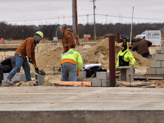 Workers lay bricks and shovel cement Dec. 29 at the under-construction site of the new McGavock automotive dealership at 818 E. Overland Trail, the north access road for Interstate 20.
