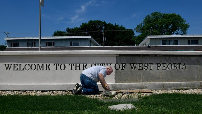 West Peoria Mayor Jim Dillon refills his brush while adding a coat of paint to the city's sign on Western Avenue in this file photo.