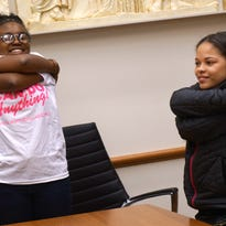 Cheris Lockett, a youth ambassador for Girls Can Do Anything shows off her shirt at a meeting.