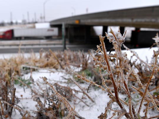 Frozen weeds and grass line Interstate 20 at the West Lake Road bridge as an 18-wheeler heads east Wednesday. The day's ice storm slowed the Big Country to a halt, closing schools and businesses across the region as sleet and freezing rain fell off an on most of the day.