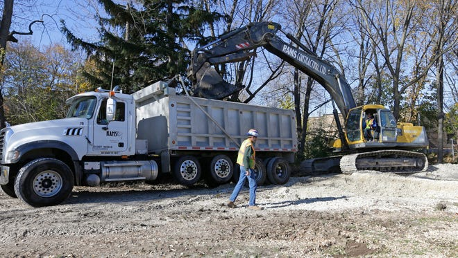 Workers with La Crosse-based J.F. Brennan Co. use excavators to remove contaminated sediment from the Ruck Pond dam raceway last week in downtown Cedarburg.