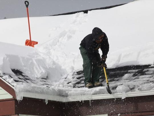 In February 2015, a roofer breaks up ice along the edge of a roof. Although this can be a fast and effective method to remove ice from a roof, most experts say it's just too risky for people without experience.