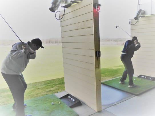 Golfers at the Swing Time driving range in Germantown