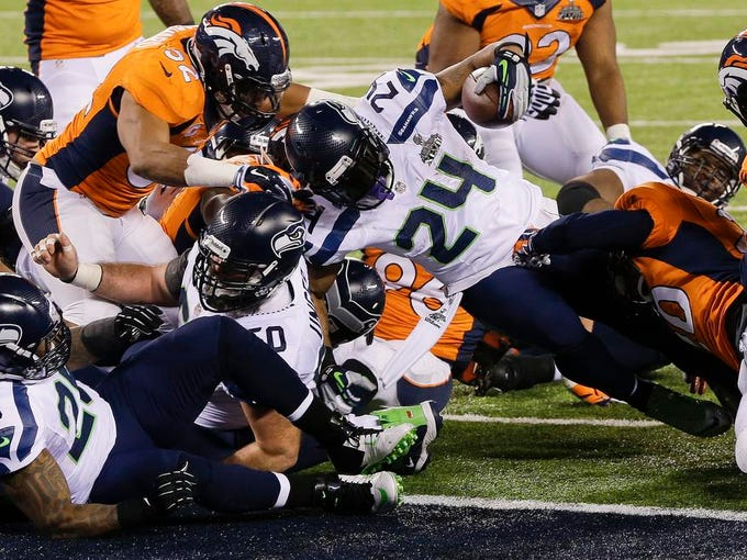Seattle Seahawks running back Marshawn Lynch (24) pushes his way into the end zone for a touchdown run against the Denver Broncos during the first half of the NFL Super Bowl XLVIII football game, Sunday, Feb. 2, 2014, in East Rutherford, N.J. (AP Photo/Chris O'Meara)